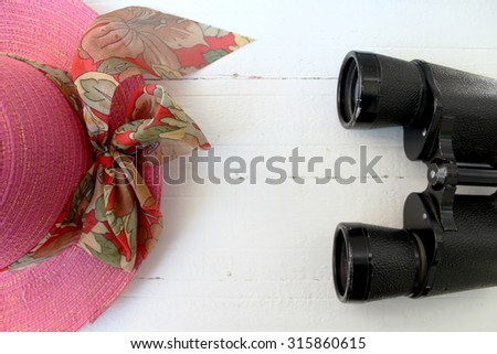 Binoculars and pink hat on white background - stock photo