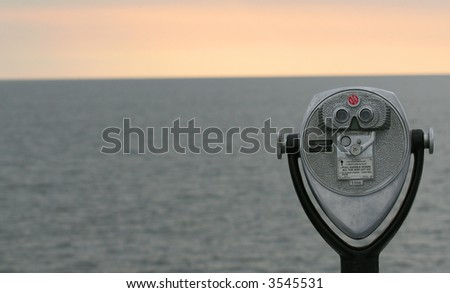 Binoculars looking out on sunrise on the ocean - stock photo