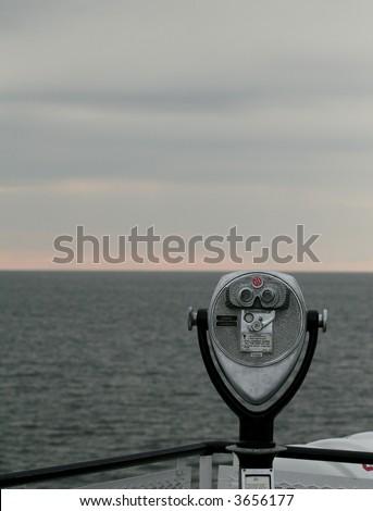 Binoculars looking out onto ocean sunrise - stock photo