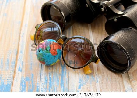 Binoculars, sunglasses and globe - stock photo