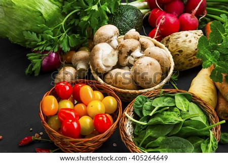 Bio and healthy vegetables assortment with tomatoes, greens, mushrooms, spinach, radish, celery and carrots - stock photo
