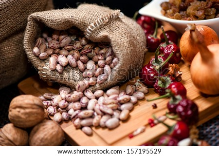 Bio onions, nuts, beans and dried pepper as food ingredients on kitchen table - stock photo