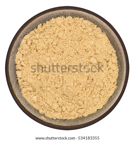 Bio organic ginger powder in ceramic bowl isolated on white background, top view