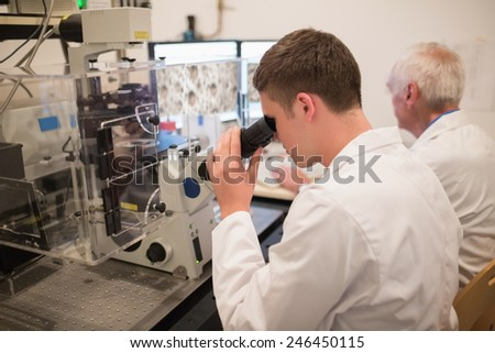 Biochemist and student looking at microscopic images on computer at the university - stock photo