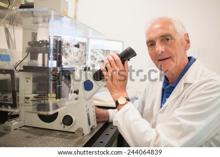 Biochemist using large microscope and computer at the university - stock photo