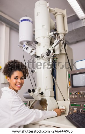 Biochemistry student using large microscope and computer at the university - stock photo