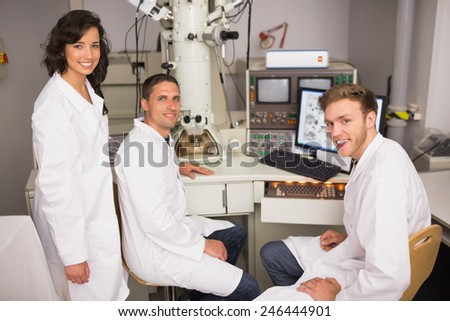 Biochemistry students using large microscope and computer at the university - stock photo