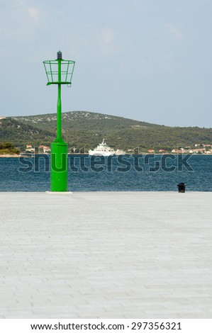 Biograd na Moru, Croatia - July 9, 2015: Green beacon located at the entrance of the harbor.