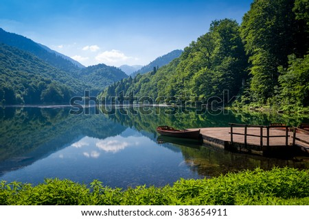 Biogradska gora national park landscape. Beautiful lake surrounded by hills and mountains with wooden pier and boats for rent. Montenegro.
