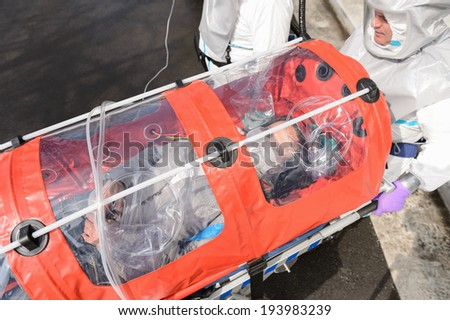 Biohazard medical team with sick patient in stretcher virus contamination - stock photo
