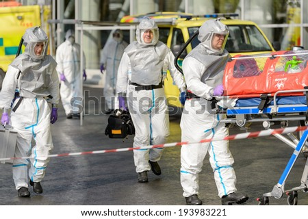 Biohazard medical team with stretcher walking on street - stock photo