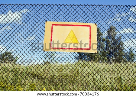 biohazard sign on the rusted fence around contaminated area - stock photo
