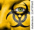Biohazard symbol painted on face with green eye to raise awareness for bio hazardous waste - stock photo