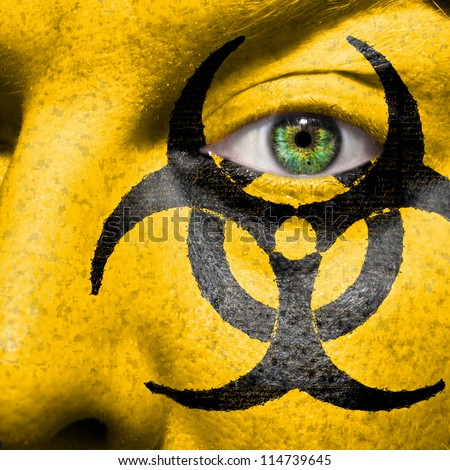 Biohazard symbol painted on face with green eye to raise awareness for bio hazardous waste