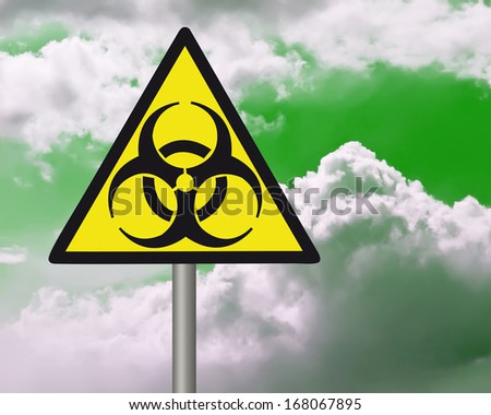 Biohazard warning sign on against dark cloudy sky. - stock photo
