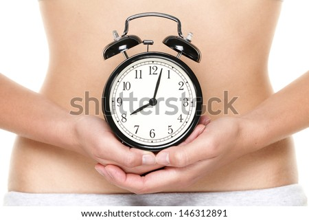 Biological clock ticking - woman holding clock in front of stomach. Biological clock and pregnancy concept with female hands and belly. - stock photo