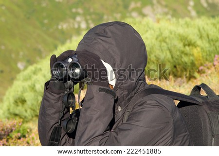 Biologist looking for wildlife using binoculars in the mountains of the north of Spain - stock photo