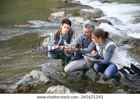 Biologist with students in science testing river water - stock photo