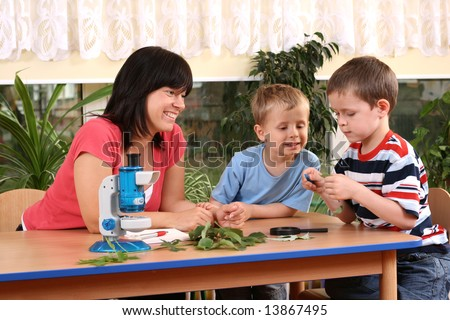 biology lesson in preschool - teacher and two boys - stock photo