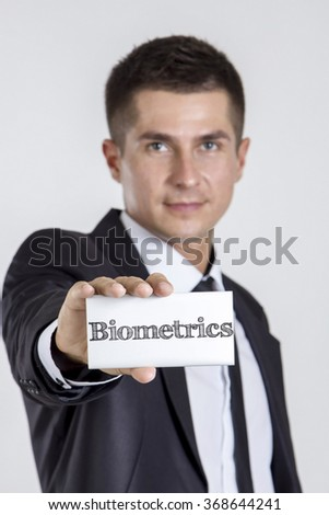Biometrics - Young businessman holding a white card with text - vertical image - stock photo