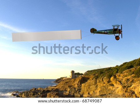 biplane pulling a blank banner on the beach - stock photo