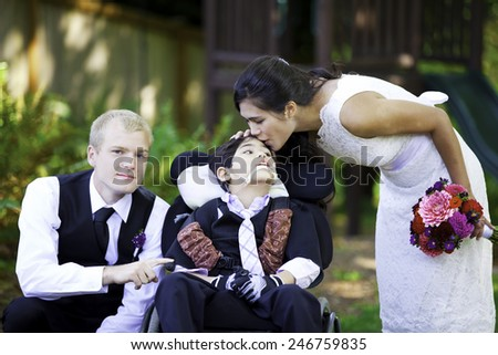 Biracial bride kissing her little brother on her wedding day. Child is disabled, in wheelchair - stock photo