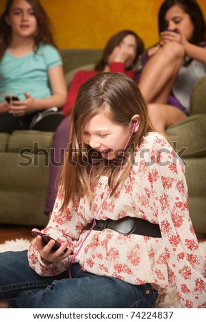 Biracial Caucasian and Asian laughs while listening to her mp3 player - stock photo