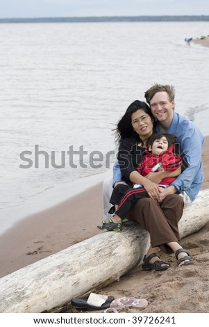 Biracial husband and wife holding their toddler at the beach