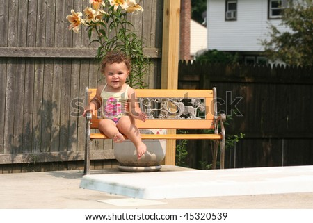 Biracial Toddler sitting by swimming pool - stock photo
