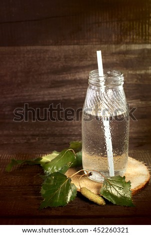Birch juice in bottles with straws on a wooden surface.