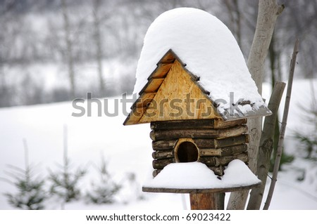 Bird box under snow during the winter - stock photo