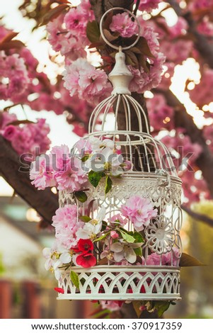 Bird cage with spring blossom of sakura and fruit flowers. Wedding decorations outdoors in the garden