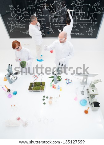 bird-eye of four people in a chemistry lab conducting experiments , analyzing substances around a lab table and writing on a blackboard - stock photo