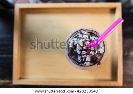 Bird eye view of Chocolate milk shake with whipped cream served on the wooden tray - stock photo