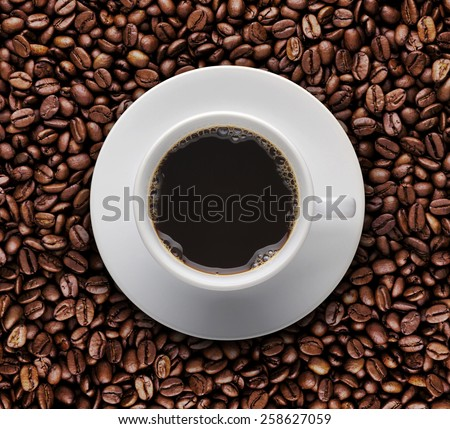 Bird eyes view of coffee cup on raw coffee beans. Top view of cup of hot coffee on roast coffee bean - stock photo