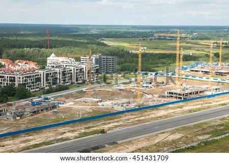 Bird's-eye shot of construction site. Modern city landscape with tower cranes