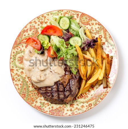 Bird's eye view of grilled rib-eye beef steak served with mushroom sauce, salad and potato chips. - stock photo