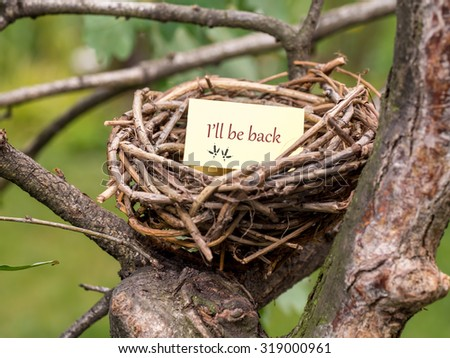 Bird's nest with I'll be back notice card - stock photo