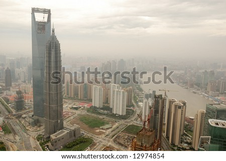 Bird view at Shanghai China. Skyscraper under construction in foreground. Fog, overcast sky and pollution. Bund (Pudong) area.