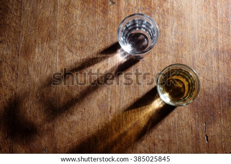 Bird view of two  shot glasses of Brazilian gold and white cachaca isolated on rustic wooden background with long shadow