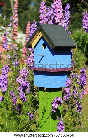 Birdhouse among flowers - stock photo