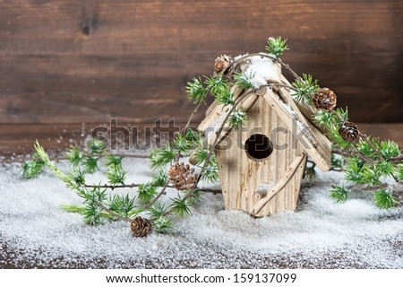 birdhouse and christmas tree brunch decoration over rustic wooden background. vintage country style picture with snow - stock photo
