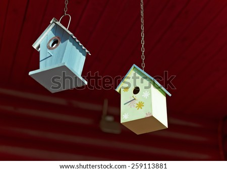 Birdhouses hanging from the roof of a country house - stock photo