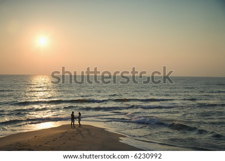 Birds eye view of couple on beach in Bald Head Island, North Carolina during sunset. - stock photo