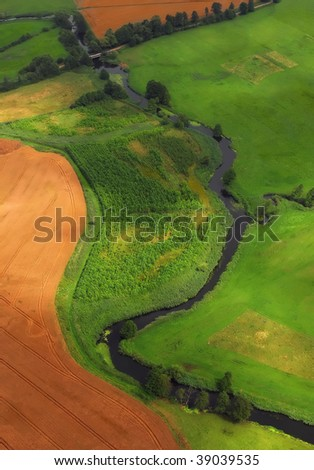 Birds view of plain countryside with small river. Summer time. - stock photo