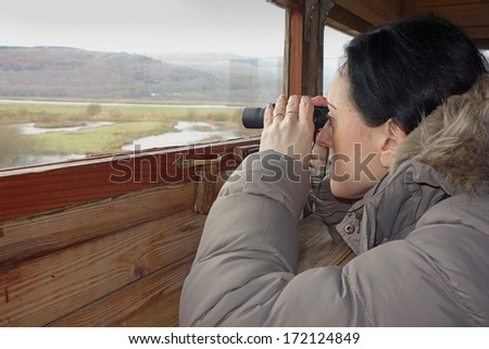 birdwatching, a woman with binoculars looking through window in bird hide - stock photo