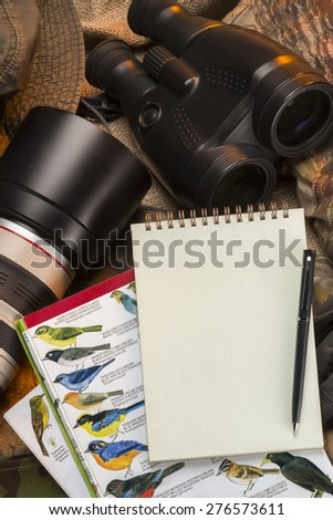 Birdwatching - Binoculars, camera, bird books and a notebook and pen - Space for text - stock photo
