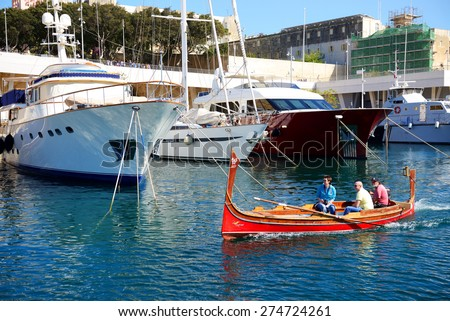 BIRGU, MALTA - APRIL 22: The traditional Maltese boat for tourists cruises on April 22, 2015 in Birgu, Malta. More then 1,6 mln tourists is expected to visit Malta in year 2015. - stock photo
