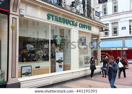 BIRMINGHAM, UK - APRIL 19, 2013: People walk by Starbucks Coffee cafe in Birmingham, UK. Starbucks Corporation operates 23,768 places worldwide. - stock photo