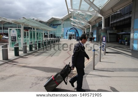 BIRMINGHAM, UK - APRIL 19: Traveler hurries on April 19, 2013 at Birmingham International Airport, UK. With 8.9 million travelers served it was the 7th busiest UK airport in 2012. - stock photo